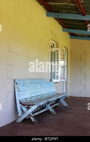 An old wooden bench on a veranda - Stock Photo