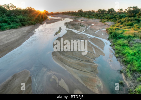 A river bed with seasonal water flowing around sand banks - Stock Photo