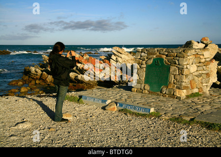 Tourist taking photo of the monument at Cape L'Agulhas -  southernmost tip of Africa where Atlantic meets Indian - Stock Photo