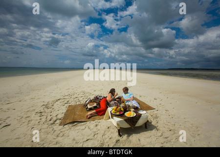 Couple enjoying beach picnic on deserted beach - Stock Photo