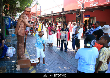 Tourists at the Victoria and Alfred Waterfront watching a street mime artist - Stock Photo