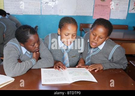 Three high school girls studying together in a classroom in a rural Kwazulu Natal school - Stock Photo