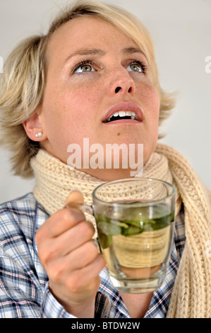 Woman gargling with sage tea - Stock Photo