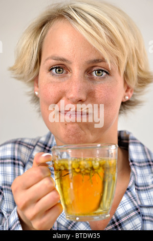 Woman rinsing her mouth with camomile tea - Stock Photo