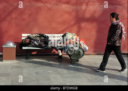 A female Chinese woman walks past a homeless Chinese man who sleeps on a park bench in Tiananmen square, Beijing - Stock Photo