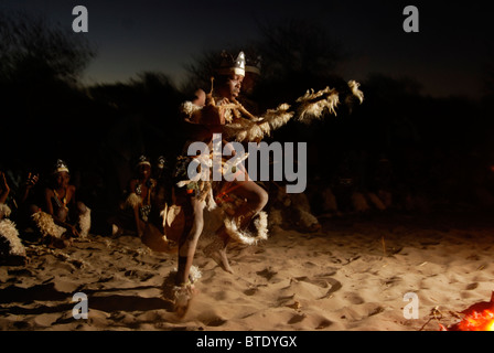 Young Zulu boy dancing around the fire in front of a row of seated boys - Stock Photo
