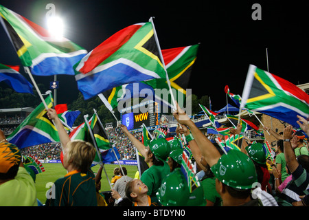 Cricket fans waving South African flags at a Pro20 international cricket match - Stock Photo