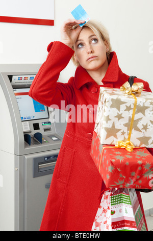 Woman with Christmas gifts in front of cashpoint - Stock Photo
