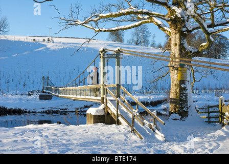Woman on footbridge over the River Wharfe, near Hebden, Wharfedale, Yorkshire Dales National Park, North Yorkshire, - Stock Photo