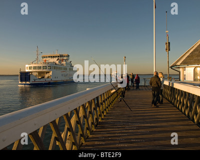 Wightlink car ferry Wight Light passing Yarmouth pier Isle of Wight England UK late afternoon - Stock Photo
