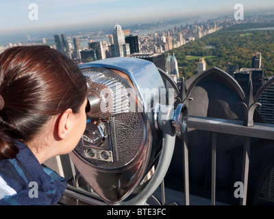 Woman looking at  Central Park from coin operated binoculars on Top of The Rock  at Rockefeller Center in Manhattan - Stock Photo