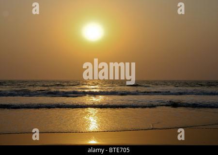 Golden sunset over the ocean waves Varca beach, Goa, India - Stock Photo
