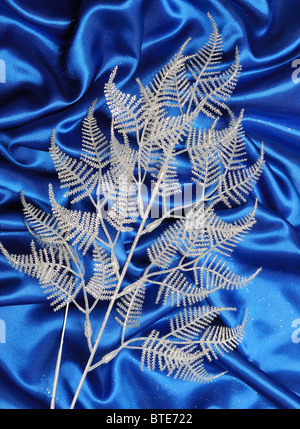Christmas decoration on blue sateen with big stars on tinsel - Stock Photo