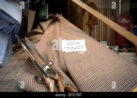 Made to measure sign in a traditional tailor's shop window in Bologna Italy. - Stock Photo