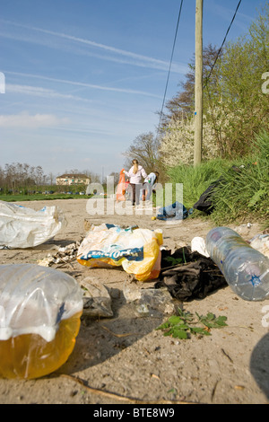 Trash dumped on dirt road, volunteers in background cleaning up - Stock Photo