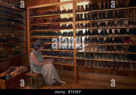 A lady customer tries on shoes at legendary leatherwork shop near Curry's Post on the Natal Midlands Meander Tourist - Stock Photo