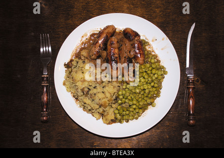 Bangers and mash, a dish consisting of sausage, mashed potatoes and peas - Stock Photo