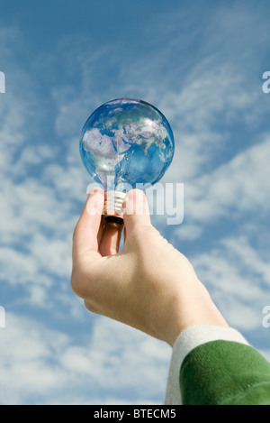 Person holding light bulb in front of sky - Stock Photo