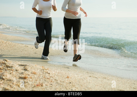 Female friends running at the beach, cropped - Stock Photo