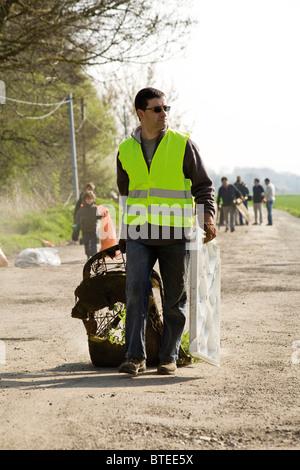 Volunteer cleaning up garbage dumped alongside road - Stock Photo