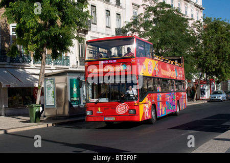 A Citysightseeing Portugal open top double deck bus carries tourist theough the Restaurdores area of Lisbon - Stock Photo