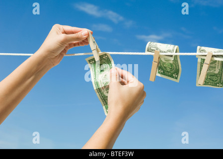 Hanging dollar bills on clothes-line - Stock Photo