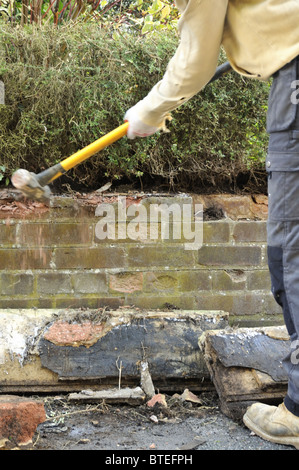 Knocking down old brick garden wall with hammer. - Stock Photo