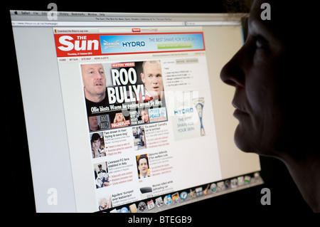 Woman reading The Sun newspaper online - Stock Photo
