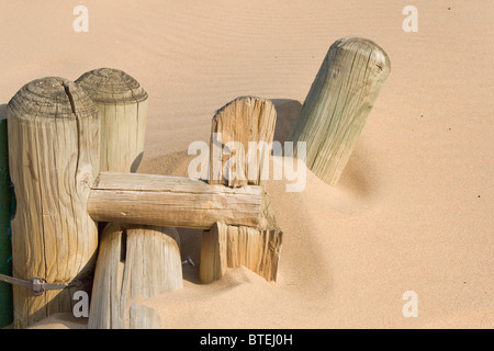 Old wooden fence poles half buried in beach sand - Stock Photo