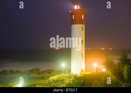 The lighthouse at Umhlanga Rocks with lit up ships lying at anchor out to sea - Stock Photo