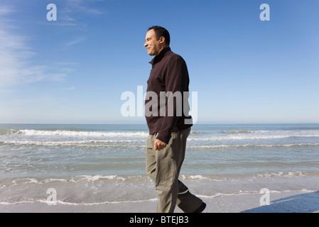 Mature man walking on beach - Stock Photo