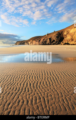 Chapel Porth beach on the north coast of Cornwall captured at low tide with St Agnes Head and Wheal Coates in the - Stock Photo