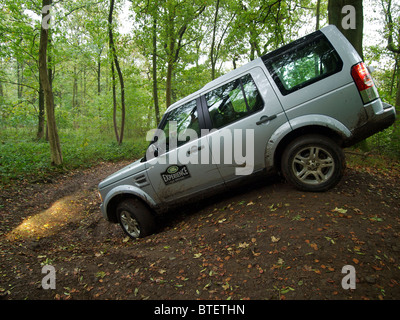 Silver Land Rover Discovery 4 driving through a forest at the Domaine d'Arthey estate in Belgium - Stock Photo