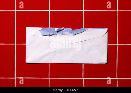 A used postal mailing envelope torn open. Red tiled background - Stock Photo