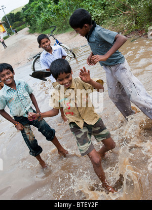 Indian children jumping and splashing in water on a flooded road in Andhra Pradesh, India - Stock Photo