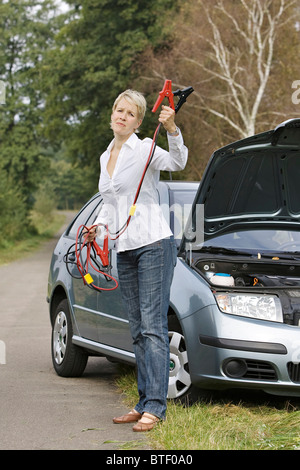 Woman beckoning with jumper cable - Stock Photo