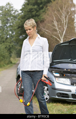 Woman holding jumper cable - Stock Photo