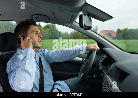 Driver phoning during car drive - Stock Photo