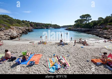 People sunbathing. Cala Sa Nau beach. Felanitx. Mallorca Island. Spain - Stock Photo