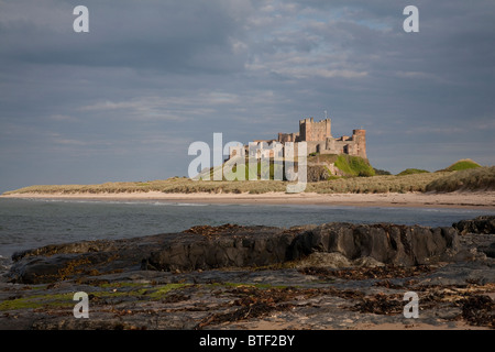 Bamburgh Castle Northumberland on its rocky plateau viewed from the beach on a late evening in summer - Stock Photo