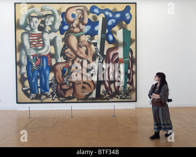 Woman looking at painting Composition aux deau Perroquets by Fernand Leger at Pompidou centre modern art museum - Stock Photo