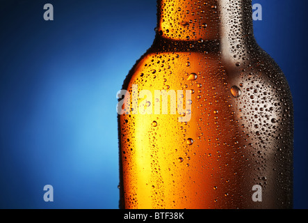 Bottle of beer with drops on a blue background. Close up part of the bottle. - Stock Photo
