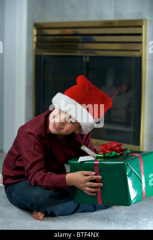 A boy trying to figure out what is in the gift box - Stock Photo