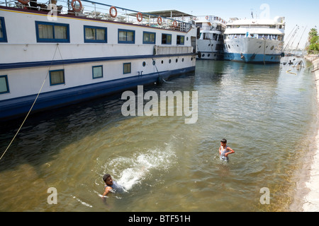 Egyptian children swimming in the river Nile near cruise ships, Luxor, Upper Egypt - Stock Photo