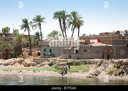 Egypt lifestyle; houses palm trees and children playing on the banks of the River Nile between Aswan and Luxor, - Stock Photo