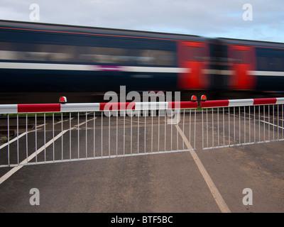 Train Speeding through Level Crossing, Northumberland - Stock Photo