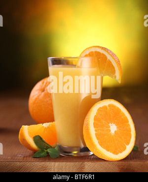 Still life: oranges and glass of juice on a wooden table. - Stock Photo
