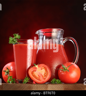Still life: tomatoes, jug and glass full of fresh tomatoes juice on wooden table. - Stock Photo