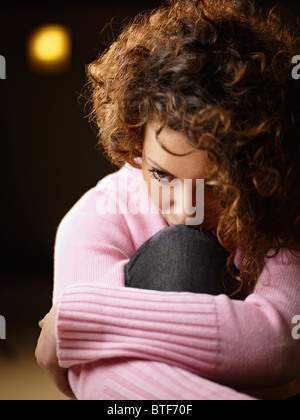 sad woman sitting on floor holding knees - Stock Photo