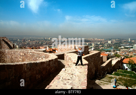 Young boy playing on the walls at the top of Ankara castle, Turkey with the capital city in the background below - Stock Photo